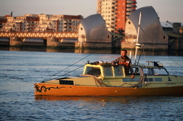 Adventurer Jason Lewis pedalling his boat Moksha on the River Thames